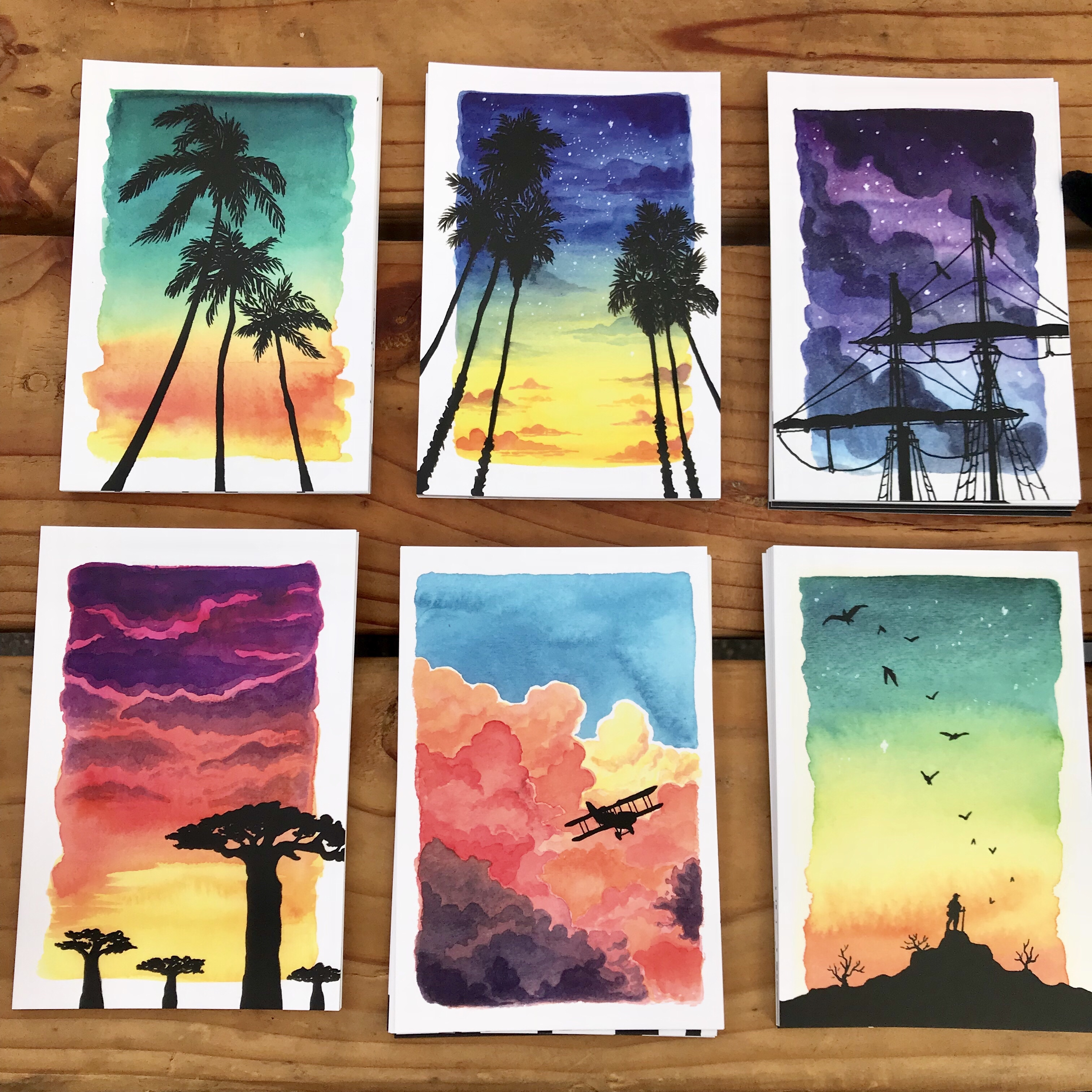 A selection of vibrant postcards featuring watercolor paintings of sunrises and sunsets with silhouettes of trees, tall ships, mountains, and other organic shapes in the foreground.
