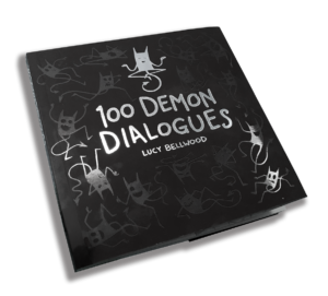 A softcover copy of 100 Demon Dialogues, a black book with silvery demons on the front.