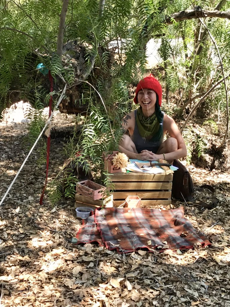 Shing, a nonbinary person in a bright red hat sits underneath a pepper tree. They have a spread of crates in front of them.