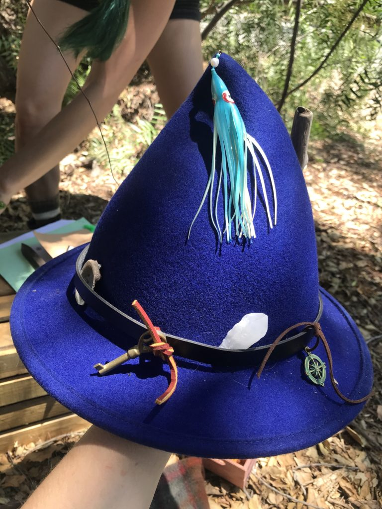 A pointy blue felt hat with a variety of nautical items attached to it.