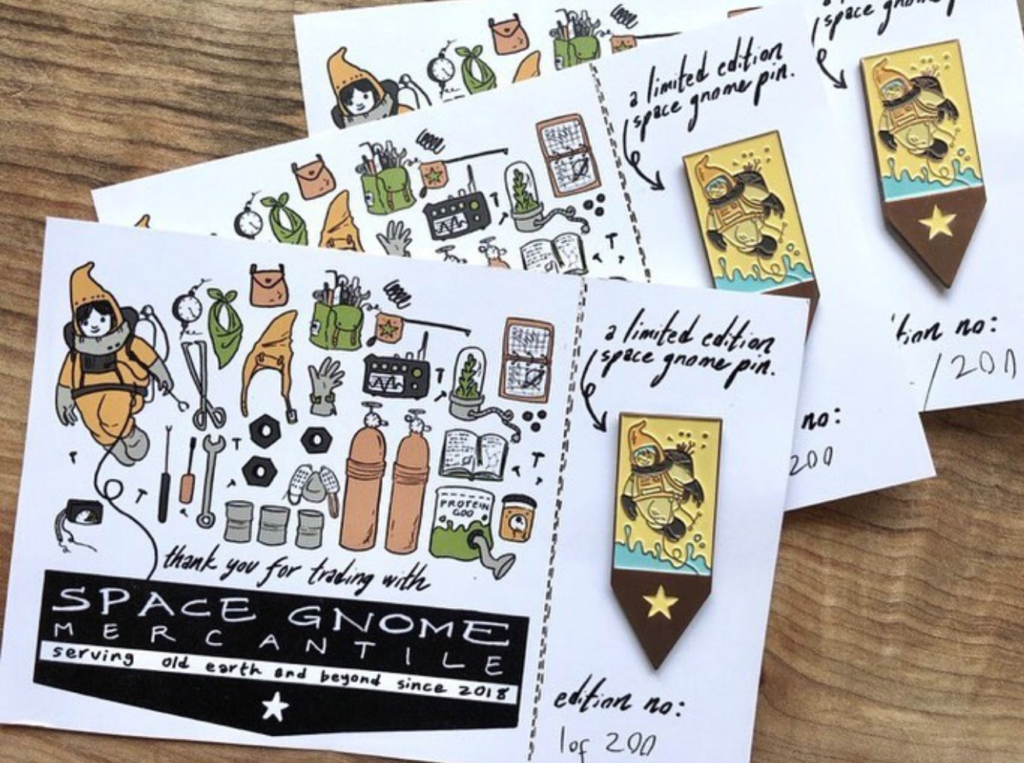 A set of postcards with enamel pins depicting a space gnome.