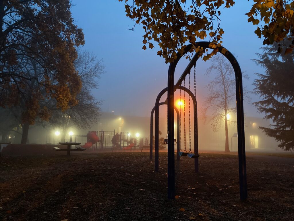 A photograph of a swing set at dusk. There's heavy mist in the air. Yellow street lights cut through the fog. There's a play structure barely visible in the distance. The photo looks wintry and chilly.
