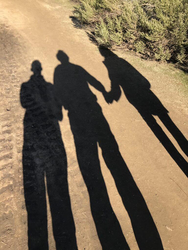 Three elongated human shadows, holding hands and walking along a dusty trail.
