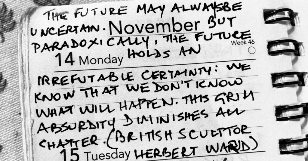 "A black and white photograph of a small notebook with a handwritten quote on Monday the 14th of November. ""The future may always be uncertain. But paradoxically, the future holds an irrefutable certainty: we know that we don't know what will happen. This grim absurdity diminishes all chatter."" (British sculptor Herbert Ward)"