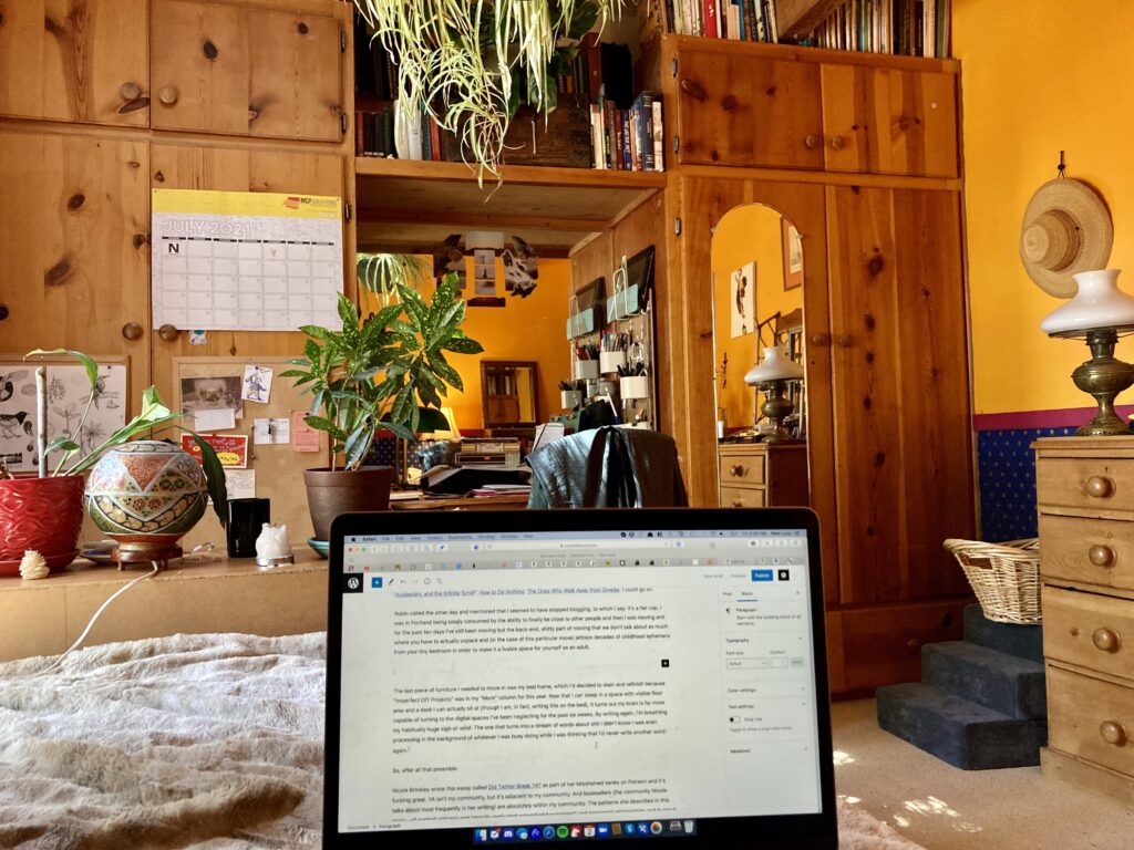 A POV photo from Lucy's bed. Her laptop is open in the forground with this blog post on it. There are wooden cabinets and a lot of books and orange walls and houseplants. It's cozy and warm.