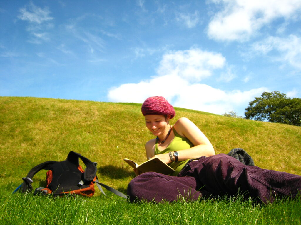 A saturated photo of Lucy on a green hillside on a sunny day. She's lying on the grass reading a book, a small orange backpack on the turf next to her.