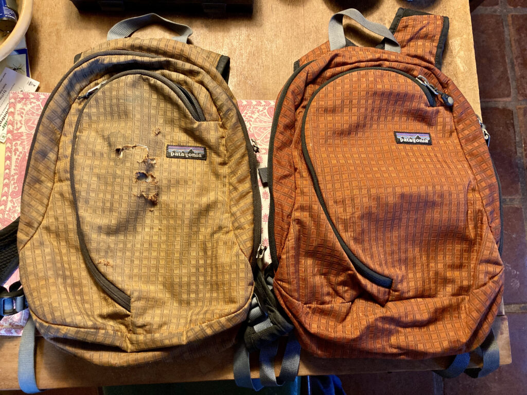 Two small Patagonia backpacks side by side. They're identical, but the one on the left is faded to a light brown with tears across the front. The one on the right is newer-looking, vibrant orange.
