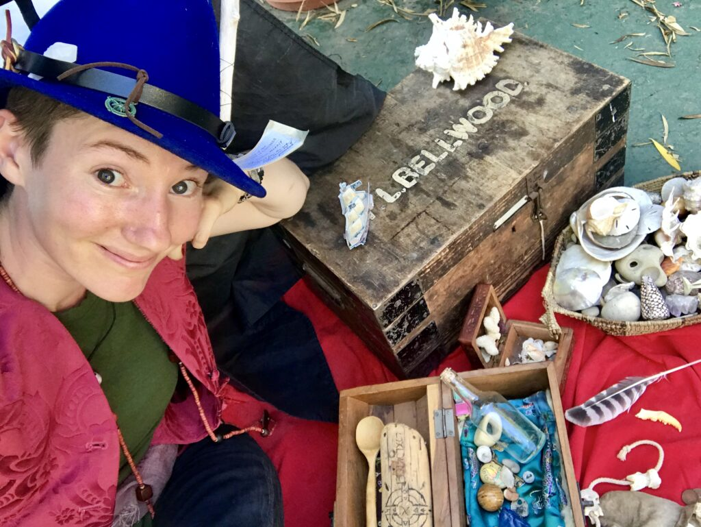 A photo og Lucy dressed up as The Boat Gnome. She wears a pointy blue felt hat covered in nautical rubbish and poses in front of many delightful trinkets, shells, and other treasures.